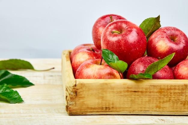 Frutos de maçãs maduras vermelhas frescas na caixa de madeira