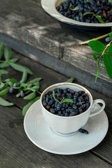 Frutos de madressilva em xícara de chá na escada de madeira ao ar livre