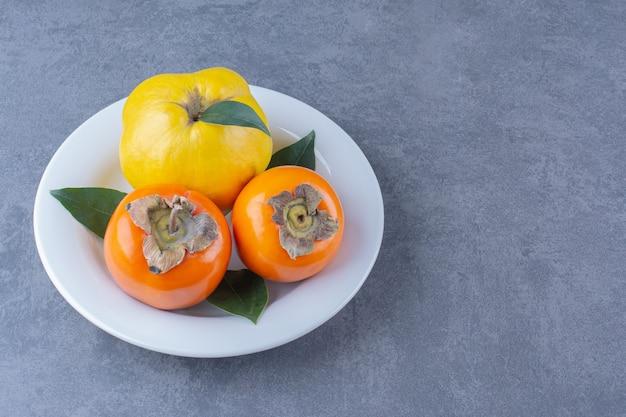 Frutos de marmelo e caqui no prato na superfície escura