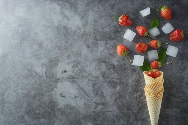 Frutos de morango no cone waffle sobre vista superior de fundo escuro