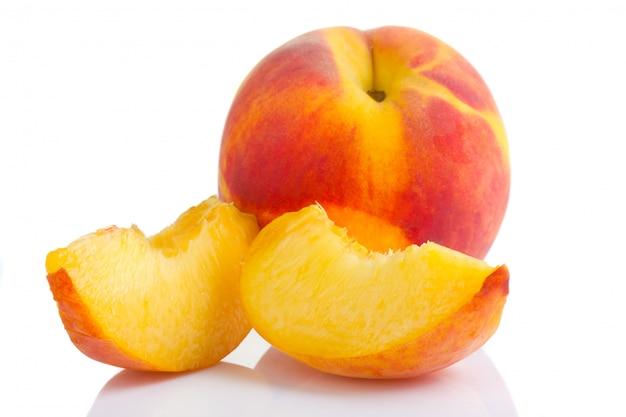 Frutos de pêssego maduros com fatias isoladas no branco