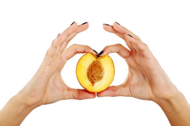 Frutos de pêssego nas mãos da mulher