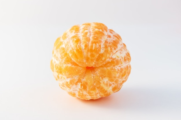 Frutos de tangerina inteira descascada ou laranja de tangerina na superfície branca