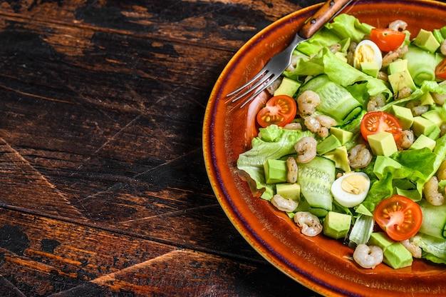 Frutos do mar, abacate, camarão, salada de camarão. mesa de madeira escura. vista do topo.