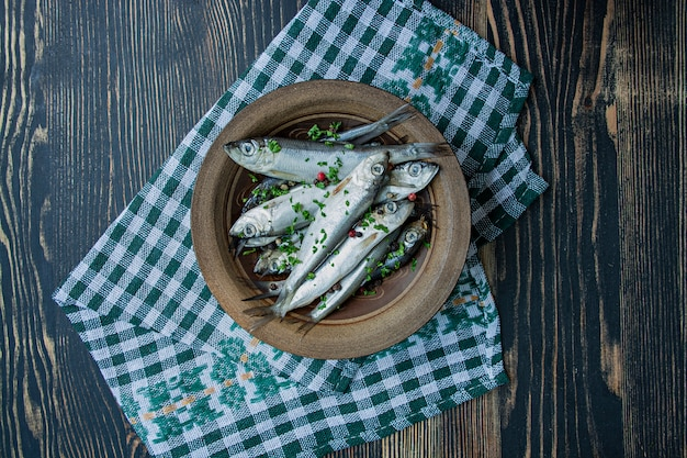 Frutos do mar arenque do báltico. peixes salgados dos arenques em uma bacia com especiarias e ervas. fundo de madeira
