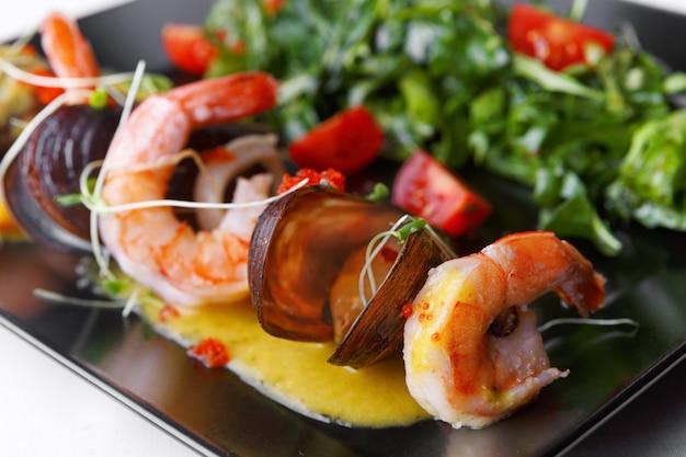 Frutos do mar, camarão, mexilhões com salada em um prato preto