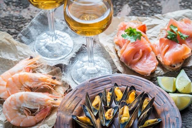Frutos do mar com dois copos de vinho branco em cima da mesa de madeira