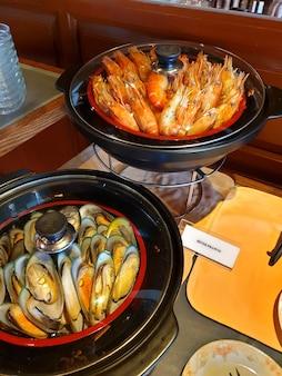 Frutos do mar deliciosos mexilhões assados com manjericão e camarão grelhado em uma panela