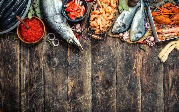 Frutos do mar diferentes com camarões e caviar vermelho. sobre um fundo de madeira.