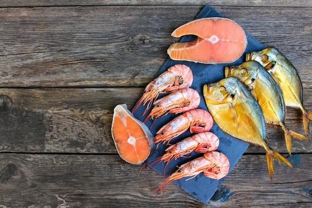 Frutos do mar diferentes: peixe, camarão no fundo antigo de madeira. vista do topo. postura plana.