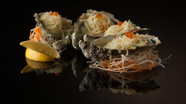 Frutos do mar e mexilhões em uma casca com queijo derretido e rodelas de limão em um fundo preto