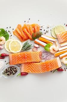 Frutos do mar frescos à mesa com especiarias, vegetais e azeite: palitos de salmão fresco e fumado, camarão e caranguejo para um supermercado ou restaurante de sushi de peixe.