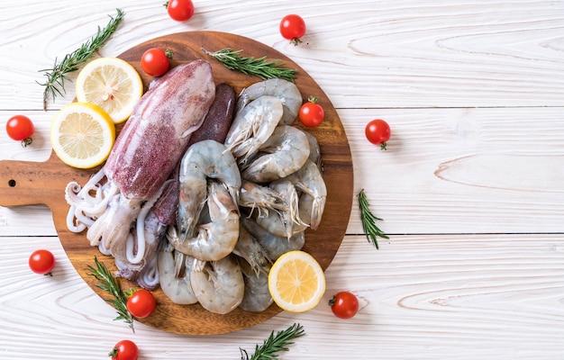 Frutos do mar frescos crus (camarões, lulas) na placa de madeira