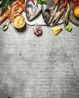 Frutos do mar frescos. diferentes peixes, camarões e mariscos com rodelas de limão e especiarias no concreto.