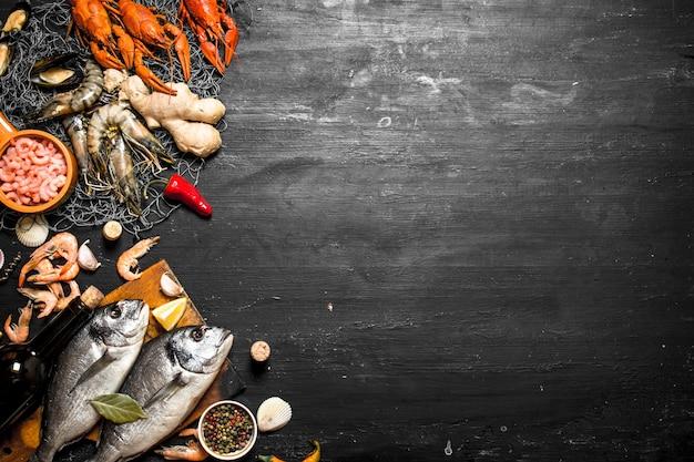Frutos do mar frescos. dois peixes frescos com uma garrafa de vinho no quadro negro.
