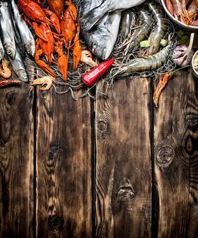 Frutos do mar frescos e crus. uma variedade de frutos do mar em uma rede de pesca. na mesa de madeira.