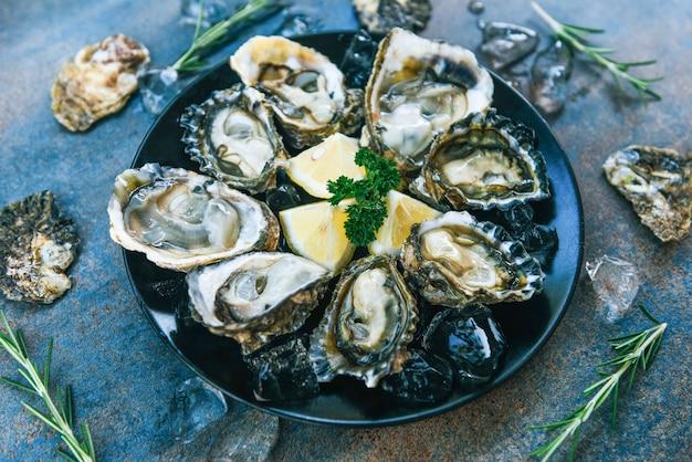 Frutos do mar frescos ostras na chapa preta. concha de ostra aberta com ervas especiarias limão alecrim servido mesa e gelo saudável comida do mar jantar de ostra crua no restaurante comida gourmet