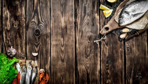 Frutos do mar frescos. peixe do mar com rodelas de limão na tábua na mesa de madeira.