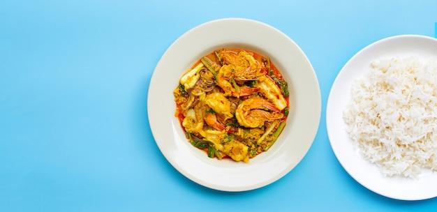 Frutos do mar fritos com caril em pó com prato de arroz sobre fundo azul.