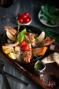 Frutos do mar grelhados em uma panela sobre uma tábua de madeira, camarão, salmão, lula com temperos e molho