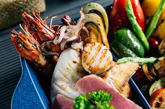 Frutos do mar misturados grelhados como peixe, lula, camarão, mexilhões e legumes.