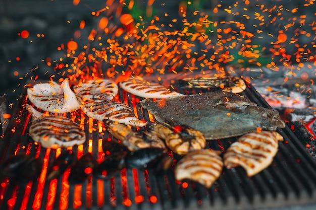 Frutos do mar na grelha, mexilhões, camarão, lula e peixe são cozidos no fogo.
