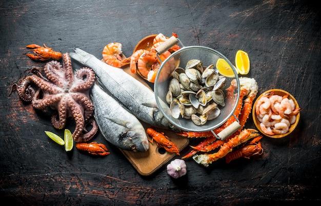 Frutos do mar. ostras, peixe fresco, camarão, polvo e caranguejo com rodelas de limão. em rústico escuro