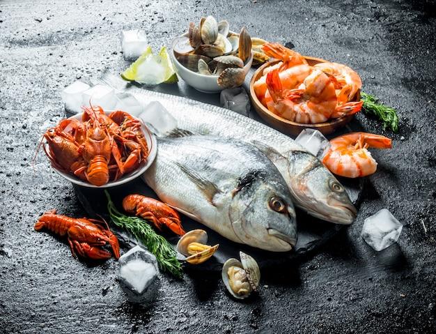 Frutos do mar. peixe fresco com camarão, lagosta e ostras numa tábua de pedra. em preto rústico