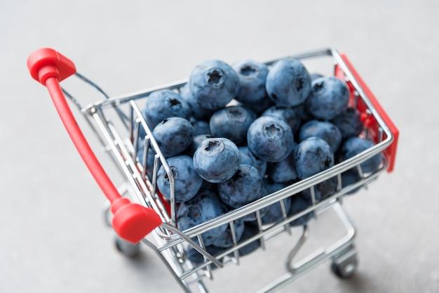 Frutos do mirtilo no mini carrinho de compras. foco seletivo sobre os mirtilos em carrinho pequeno