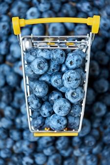 Frutos do mirtilo no mini carrinho de compras. mirtilos em carrinho pequeno