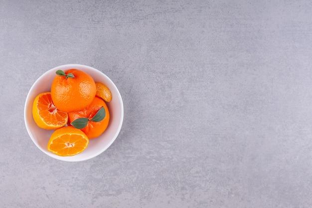Frutos inteiros de laranja com folhas verdes colocados em um prato branco.