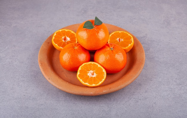 Frutos inteiros de laranja com folhas verdes colocados na superfície da pedra.