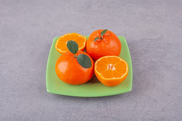 Frutos inteiros de laranja com tangerina fatiada colocados em uma pedra.