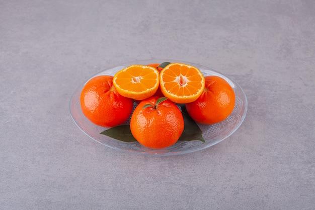 Frutos inteiros de laranja com tangerina fatiada colocados sobre uma superfície de pedra.