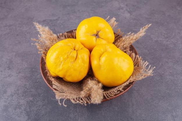 Frutos inteiros de marmelo maduros frescos colocados em uma tigela com pano de saco.