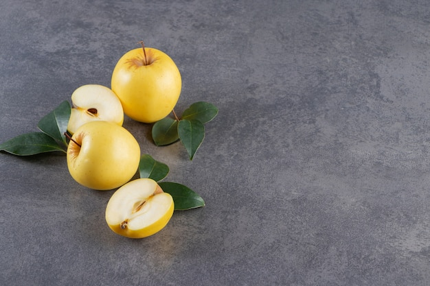 Frutos inteiros e fatiados de maçã amarela colocados na mesa de pedra.