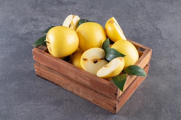 Frutos inteiros e fatiados de maçã amarela com folhas colocadas em uma caixa de madeira.