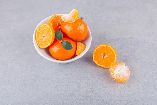 Frutos inteiros e fatiados de tangerina com folhas colocadas sobre uma mesa de pedra.