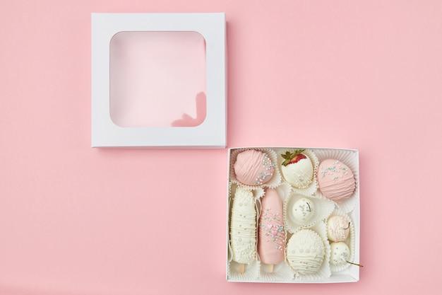 Frutos maduros cobertos com chocolate rosa e branco estão em uma caixa em um fundo rosa. vista de cima