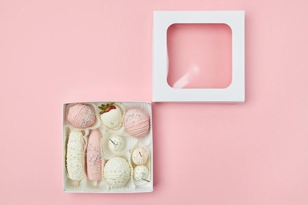 Frutos maduros cobertos com chocolate rosa e branco mentem em uma caixa
