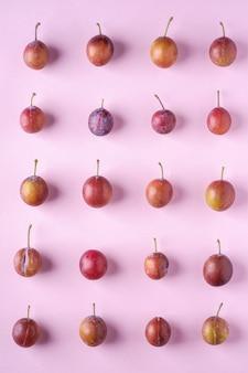 Frutos maduros de ameixa doce padrão textura, vista superior, fundo liso leigo, rosa