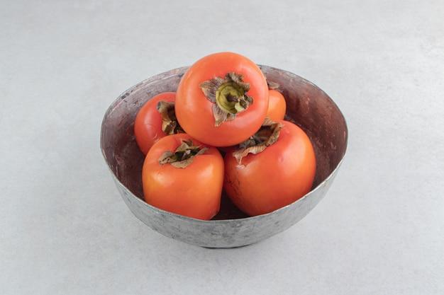 Frutos maduros de caqui em uma tigela de metal.
