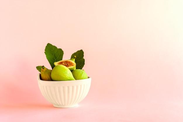 Frutos maduros de figo amarelo com folhas em uma tigela de cerâmica branca sobre fundo claro