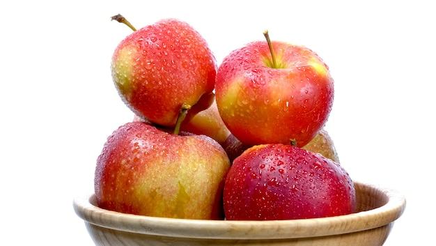 Frutos maduros de maçã jardim no cesto na mesa de madeira.