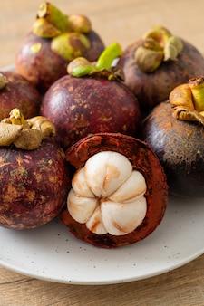 Frutos maduros de mangostão em prato branco