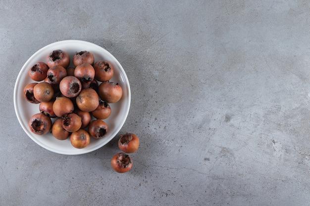 Frutos maduros de nêspera colocados no fundo de pedra.