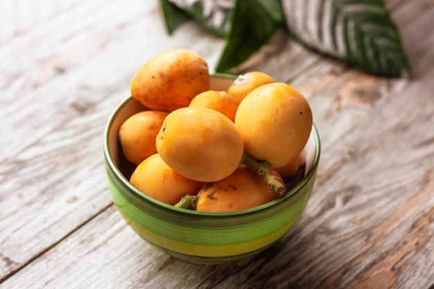 Frutos maduros de nêspera (eriobotrya japonica) e folhas verdes de nêspera na mesa de madeira.