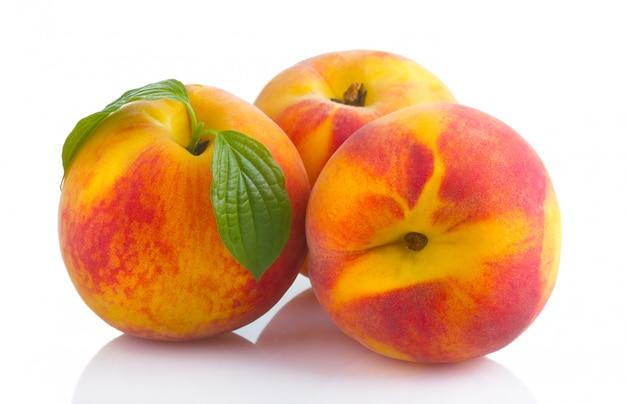Frutos maduros de pêssego com folhas verdes isoladas