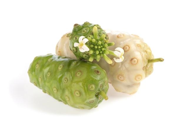 Frutos maduros de um noni cru e flores isoladas no fundo branco.