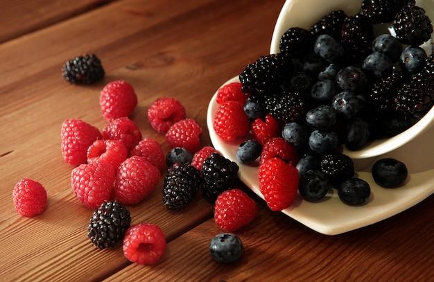Frutos maduros e doces diferentes em uma tigela branca sobre uma mesa de madeira rústica conceito de colheita framboesas vermelhas